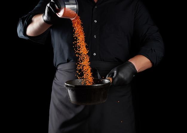 Повар в черной одежде и латексных перчатках наливает сырую чечевицу в круглую чугунную сковороду.