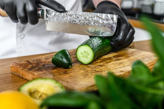 Шеф-повар в черных перчатках режет свежий зеленый огурец на деревянной разделочной доске