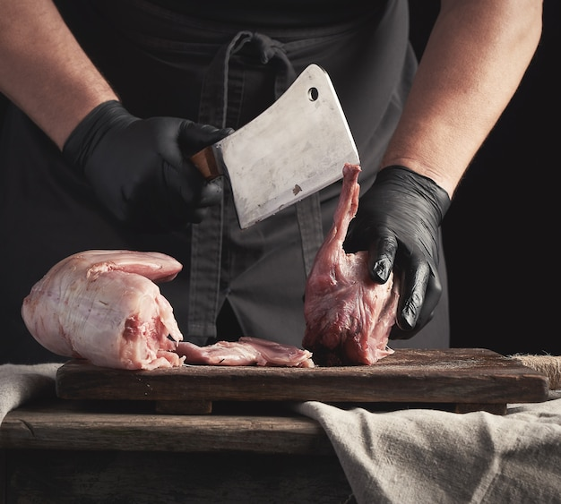 黒いラテックス手袋のシェフが大きなナイフを持ち、生のウサギ肉に切り分けます