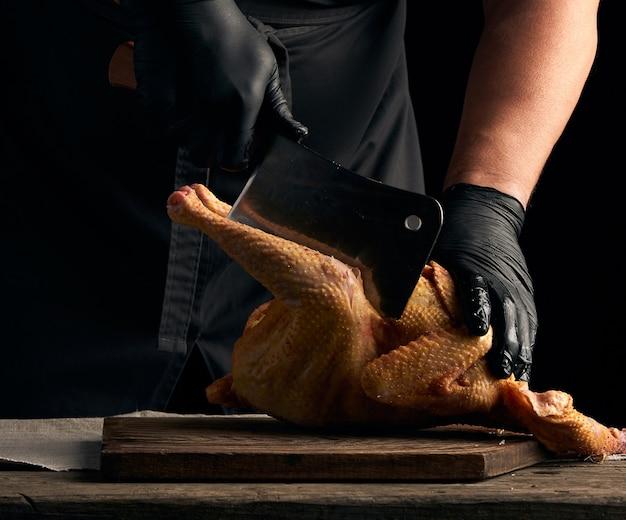 Шеф-повар в черной униформе и латексных перчатках, нарезая кусочки сырой курицы