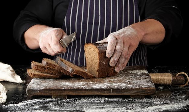 Шеф-повар в черной форме держит в руке кухонный нож и отрезает куски хлеба от испеченного коричневого ржаного хлеба