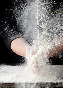 Шеф-повар в черной форме разбрызгивает белую пшеничную муку в разные стороны