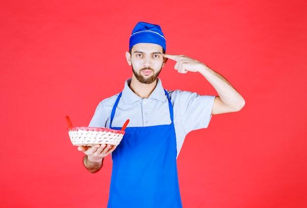 赤いタオルで覆われたパンかごを持って考えている青いエプロンのシェフ。