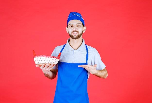 赤いタオルで覆われたパンかごを持っている青いエプロンのシェフ。