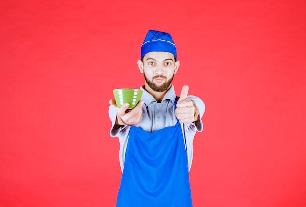 緑のセラミックカップを保持し、満足のサインを示す青いエプロンのシェフ。