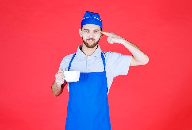 白いセラミックカップを持って考えている青いエプロンのシェフ。