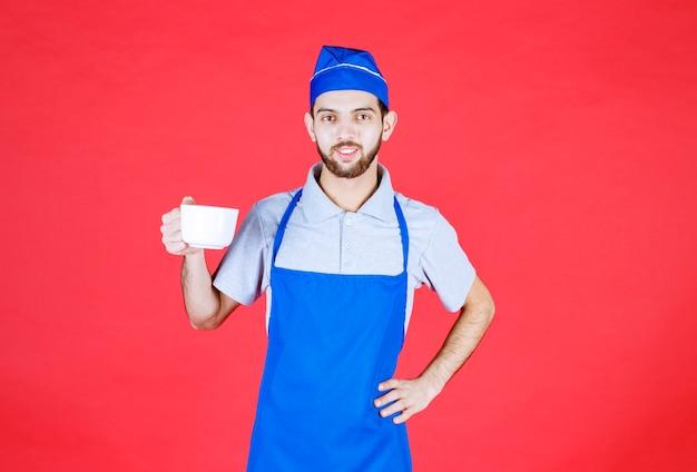 白いセラミックカップを持っている青いエプロンのシェフ。