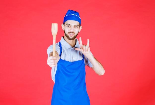 Шеф-повар в синем фартуке держит деревянную лопатку и показывает знак удовольствия.
