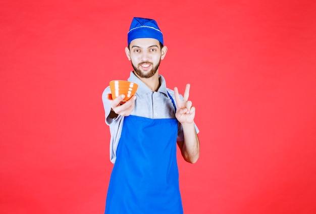 Шеф-повар в синем фартуке держит желтую керамическую чашку и знак удовольствия showign.