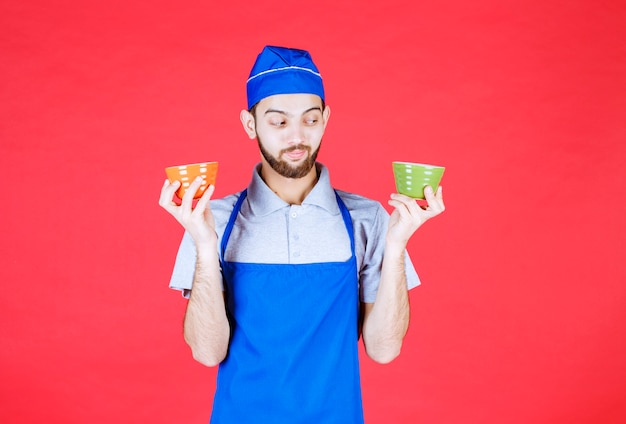 Повар в синем фартуке, держа желтые и зеленые керамические чашки в обеих руках.