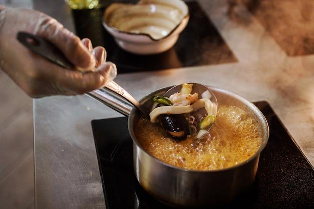 Повар в перчатках готовит вкусный суп из морепродуктов.