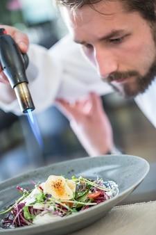 Шеф-повар на кухне отеля или ресторана жарит козий сыр на овощном салате мини-паяльная лампа