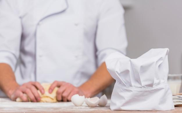 Шеф-повар на кухне делает тесто