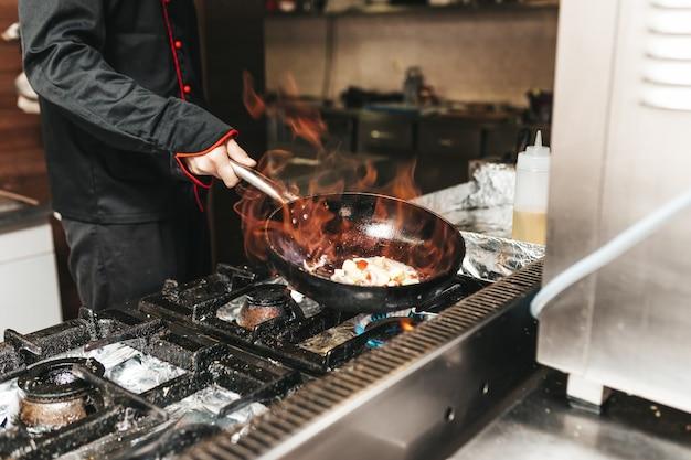 火で野菜を準備するキッチンレストランのシェフ。