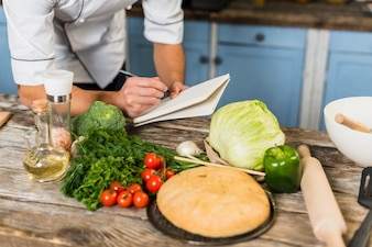 Chef in kitchen taking notes