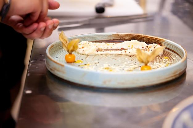 Шеф-повар ресторана готовит прекрасные блюда. приготовление вкусной еды