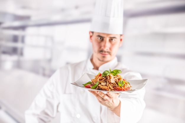イタリア料理のスパゲッティボロネーゼとプレートを保持しているレストランのキッチンのシェフ。