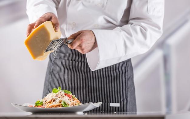 レストランの厨房のシェフがイタリアンミールスパゲッティとすりおろしたパルメザンチーズを用意しました。