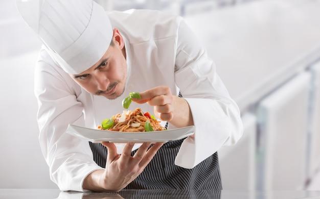 Шеф-повар на кухне ресторана готовит и украшает еду руками. готовим, готовим спагетти болоньезе.