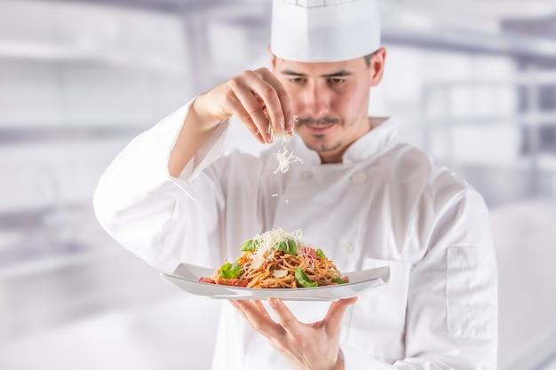 レストランの厨房のシェフが手で料理を作り、飾ります。スパゲッティボロネーゼを準備して調理します。