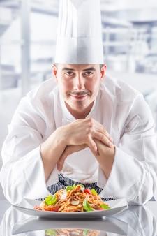 Шеф-повар в кухне ресторана с тарелкой из итальянской еды, спагетти болоньезе. Premium Фотографии
