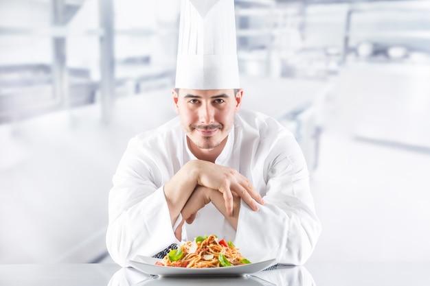 イタリア料理のスパゲッティボロネーゼのプレートを備えたレストランのキッチンのシェフ。