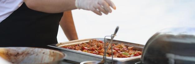 Шеф-повар в резиновых перчатках готовит еду в ресторане крупным планом