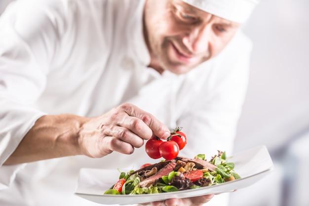 Шеф-повар на кухне отеля или ресторана украшает еду непосредственно перед подачей на стол.