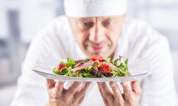 Шеф-повар на кухне отеля или ресторана держит тарелку с едой перед подачей на стол.