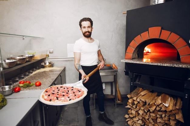 Шеф-повар на кухне готовит пиццу Бесплатные Фотографии