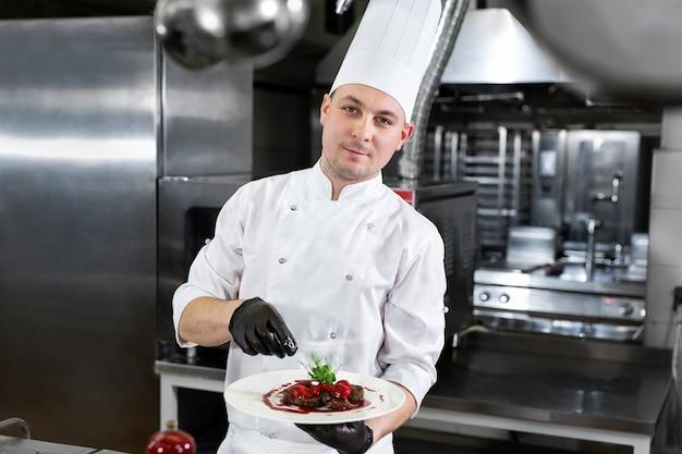 레스토랑의 요리사는 딸기와 함께 기성품 고기 요리와 함께 접시를 보유하고 있습니다.