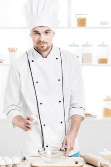 キッチンで生地を準備するためにボウルに均一なbreakseggsのシェフ