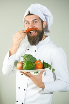 제복을 입은 요리사는 얼굴 옆에 후추를 보유하고 있습니다. 야채와 수염 된 요리사입니다. 요리와 채식.