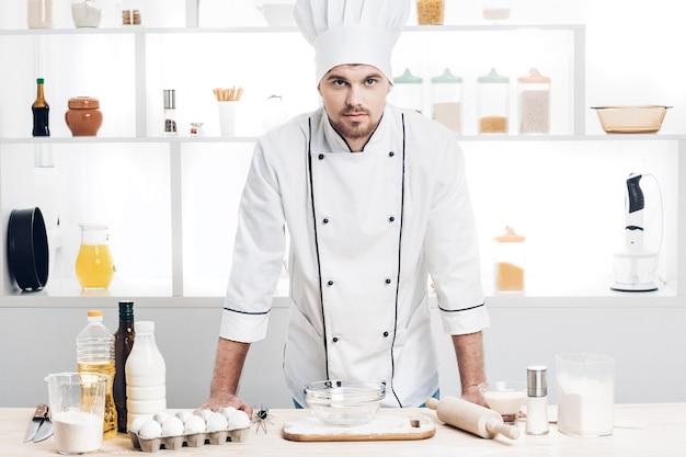 制服を着たシェフがキッチンで生地を作る準備ができています