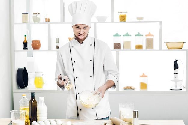 Шеф-повар в униформе делает тесто на кухне. плохое тесто