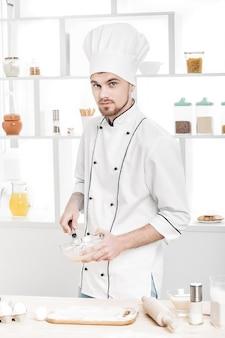 キッチンのボウルに卵とミルクを泡立てる制服を着たシェフ