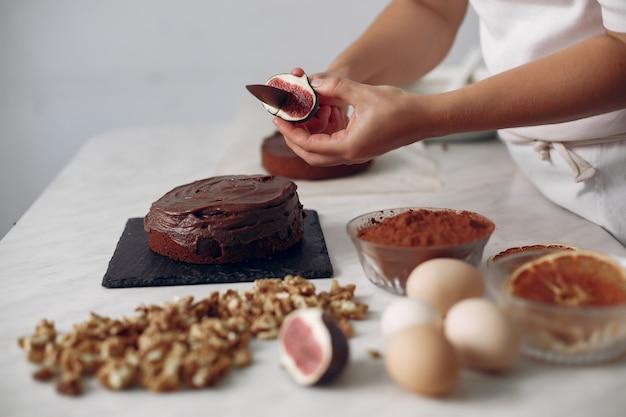 白い服を着たシェフがチョコレートケーキを用意します。女性はデザートを準備しています。女性はケーキを焼きます。
