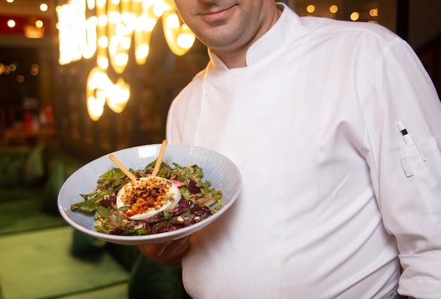 Повар в белой форме с блюдом в руке.