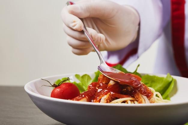 Chef is garnishing and preparing pasta dish