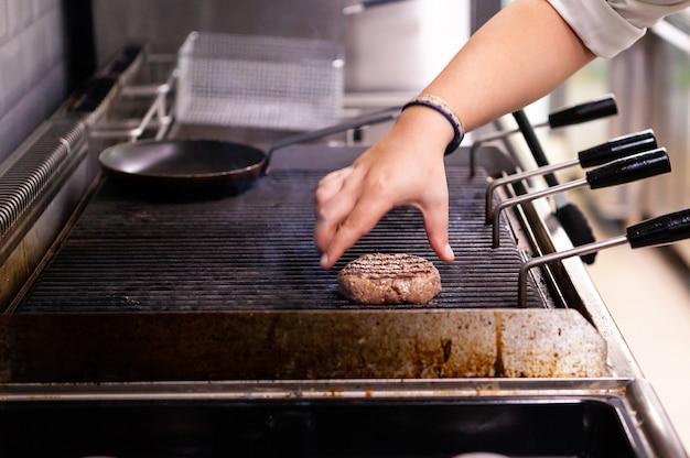 Шеф-повар готовит на гриле мясной бургер. быстрая кухня