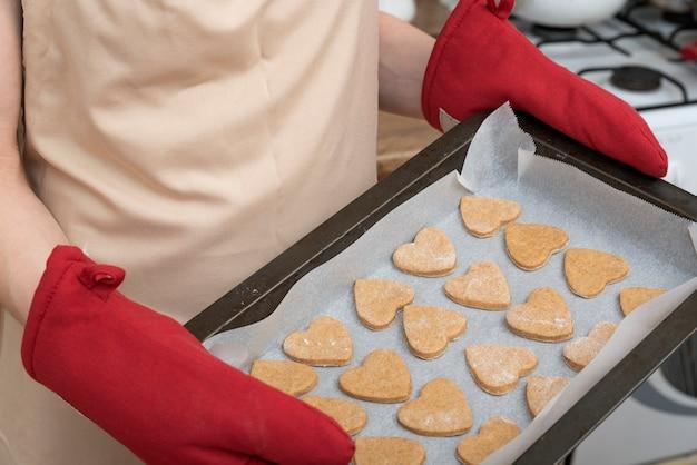 Шеф-повар держит противень с сырым песочным печеньем. процесс создания файлов cookie.