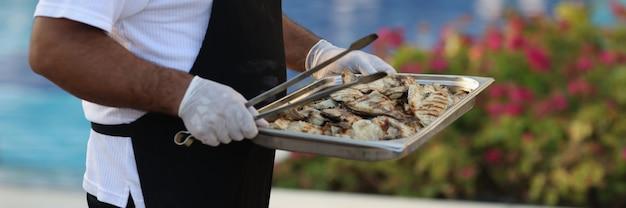 요리사는 구운 생선 화로를 들고