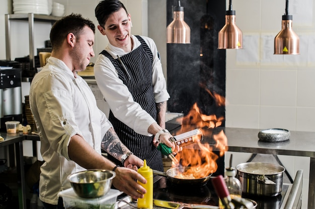 Chef is making flambe in a restaurant kitchen