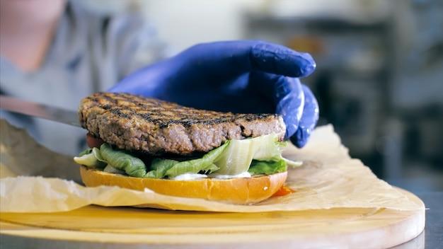 シェフはレストランのキッチンでおいしいハンバーガーを準備しています