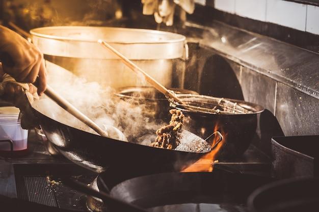 Шеф-повар перемешивает овощи в воке