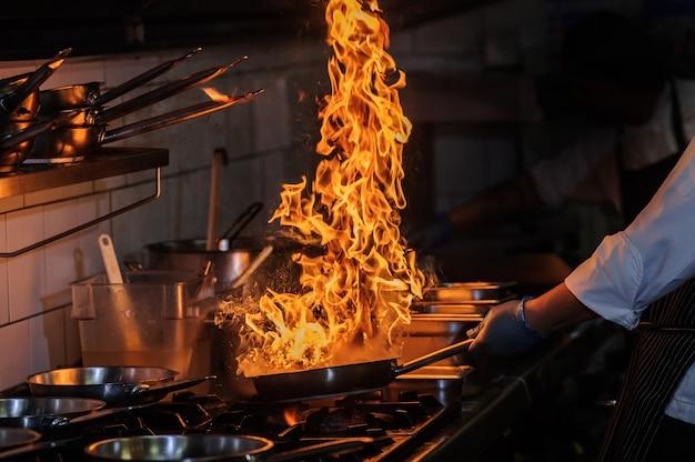 シェフが直火で中華鍋で野菜をかき混ぜています