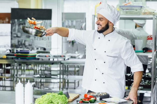 Повар жонглирует овощами и другой едой на кухне