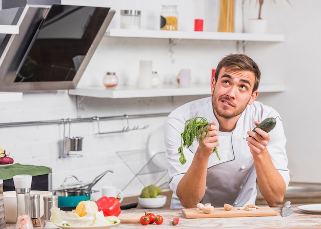Chef in kitchen cooking with vegetables