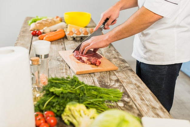 Chef in kitchen cutting meat