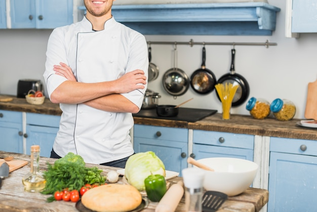 Chef in cucina di fronte a verdure